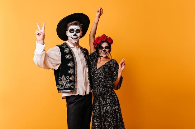 Zombie W Meksykańskich Strojach Wyrażające Szczęście. Urocza Młoda Kobieta świętuje Halloween Z Przyjacielem. Darmowe Zdjęcia