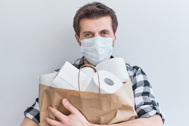 Zostań W Domu Dzięki Koncepcji Ochrony Covid-19. Mężczyzna W Masce Ochronnej Trzyma Torbę Na Zakupy Z Rolkami Papieru Toaletowego Premium Zdjęcia