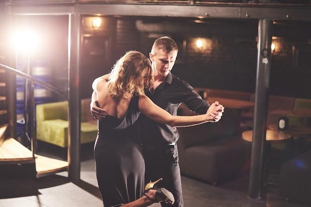 Zręczni Tancerze Występujący W Ciemnym Pokoju Pod światłem. Darmowe Zdjęcia