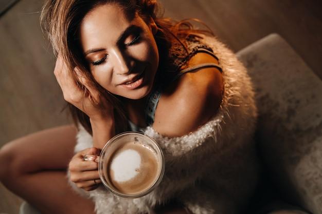 Zrelaksowana Dziewczyna Pije Kawę W Domu. Wewnętrzny Spokój. Dziewczyna Siedzi Wygodnie Na Kanapie I Pije Kawę. Premium Zdjęcia