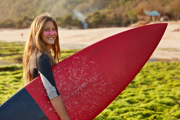Zrelaksowana Kobieta Z Cynkiem Surfowania Na Twarzy, Nosi Deskę Surfingową Darmowe Zdjęcia