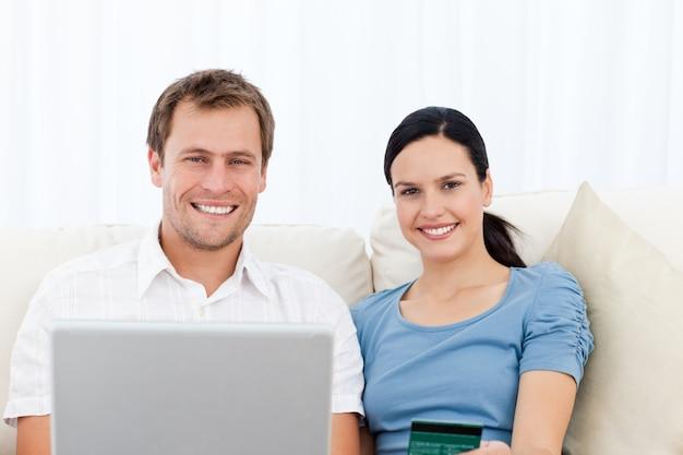 Zrelaksowana Para Z Laptopem I Kredytową Kartą Siedzi Na Kanapie Premium Zdjęcia