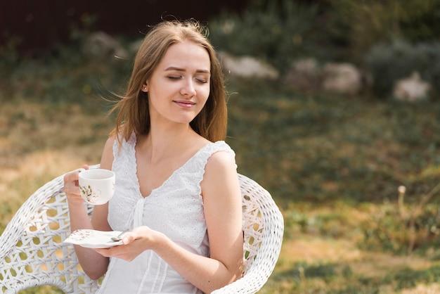 Zrelaksowana uśmiechnięta blondynki młoda kobieta cieszy się kawę w ogródzie Darmowe Zdjęcia