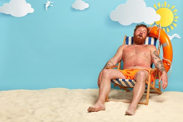 Zrelaksowany Brodaty Mężczyzna śpi Na Swoim Leżaku, Pozuje Na Plaży Darmowe Zdjęcia