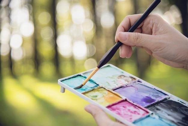 Zrelaksuj się kobieta, malowanie akwarelami dzieła sztuki w zielonym ogrodzie lasu natury Darmowe Zdjęcia