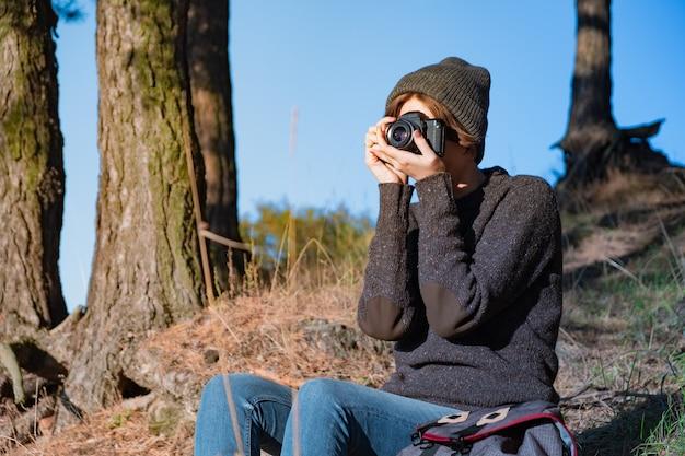 Zrobienie Zdjęcia Starym Aparatem Analogowym W Lesie. Kobieta Turysta Za Pomocą Aparatu W Scenie Pięknej Przyrody W Jasny Słoneczny Dzień Premium Zdjęcia