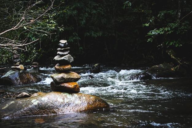 Zrównoważony Kamienny Piramidy Na Brzegu Wodospadu Górskiego Jeziora. Błękitne Góry W Lustrze Poziomu Wody. Złe Warunki Oświetleniowe. Premium Zdjęcia