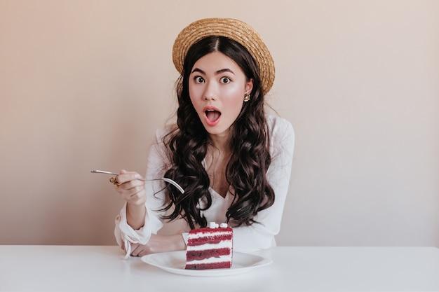 Zszokowana Azjatykcia Kobieta W Kapeluszu Je Deser. Zdziwiona Chinka Korzystających Z Ciasta. Darmowe Zdjęcia