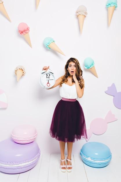 Zszokowana Dziewczyna W Spódnicy Midi Zdała Sobie Sprawę, że Goście Spóźnili Się Na Jej Przyjęcie Urodzinowe. Pełnometrażowy Portret Modnej Młodej Kobiety Z Budzikiem I Nieszczęśliwą Miną, Pozowanie W Pobliżu Słodyczy Zabawek. Darmowe Zdjęcia
