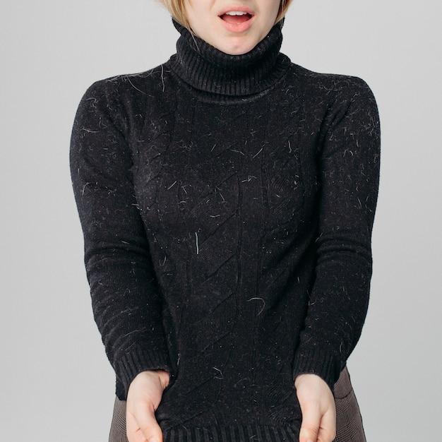 Zszokowana kobieta pokazuje jej brudny czarny sweter Premium Zdjęcia
