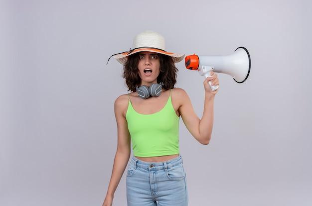 Zszokowana Młoda Kobieta Z Krótkimi Włosami W Zielonej Bluzce W Słuchawkach W Kapeluszu Przeciwsłonecznym, Zaskakująca I Trzymająca Megafon Na Białym Tle Darmowe Zdjęcia
