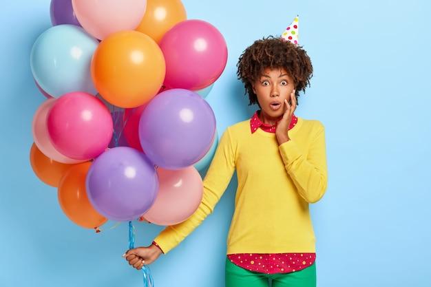 Zszokowana Piękna Młoda Kobieta Trzyma Wielobarwne Balony, Pozując W żółtym Swetrze Darmowe Zdjęcia