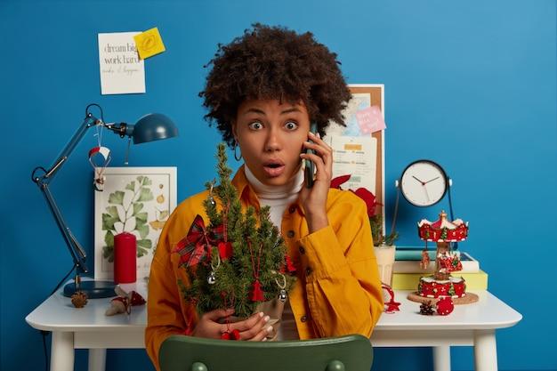 Zszokowana Przerażona Kobieta Z Fryzurą Afro, Trzyma Pięknie Udekorowaną Choinkę, Zapomina Kupić Coś Niezbędnego Na Wakacje Darmowe Zdjęcia