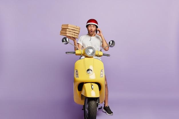 Zszokowany Dostawca Prowadzący Skuter, Trzymając Pudełka Po Pizzy Darmowe Zdjęcia