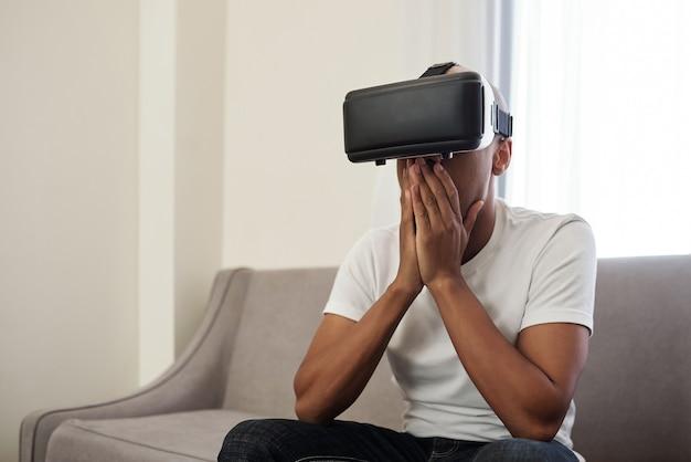 Zszokowany Emocjonalny Młody Murzyn Grający W Gry Wideo Lub Oglądający Wideo W Okularach Premium Zdjęcia