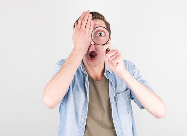 Zszokowany Mężczyzna Patrząc Przez Szkło Powiększające Premium Zdjęcia