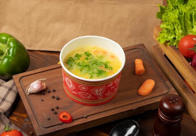 Zupa jarzynowa rosół z kurczaka w misce jednorazowego użytku z zielonymi warzywami. Darmowe Zdjęcia