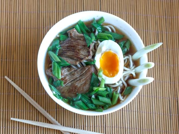 Zupa ramen ze świeżą cebulką, gotowanym jajkiem i smażonym mięsem Premium Zdjęcia