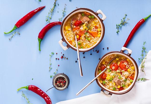 Zupa Z Małym Makaronem, Warzywami I Kawałkami Mięsa W Misce Na Niebieskim Stole. Włoskie Jedzenie. Darmowe Zdjęcia