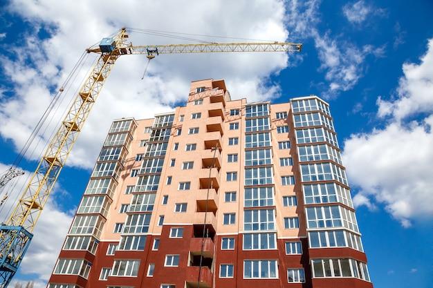 Żuraw wieżowy budynek nowy nowoczesny dom na tle niebieskiego nieba deszczu w słoneczny dzień. Premium Zdjęcia