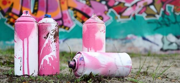 Zużyte Puszki Z Farbą Leżą Na Ziemi W Pobliżu ściany Z Pięknym Obrazem Graffiti Premium Zdjęcia