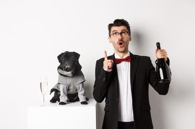 Zwierzęta, Ferie Zimowe I Koncepcja Nowego Roku. Przystojny Młody Mężczyzna W Garniturze Obchodzi Boże Narodzenie Z Czarnym Psem, Szczeniakiem Na Sobie Kostium, Właściciel Szuka I Wskazuje Na Miejsce. Premium Zdjęcia