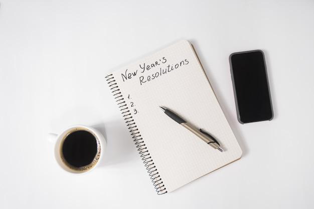 Zwrot Noworoczne Postanowienia W Notatniku I Piórze, Filiżance Kawy I Smartfonie Na Stole Premium Zdjęcia
