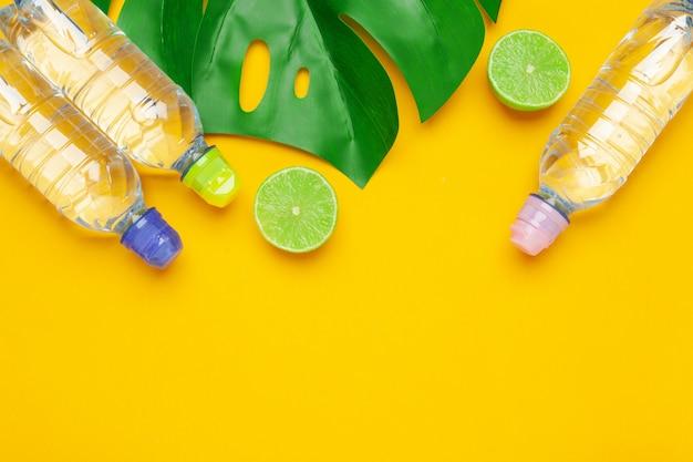 Zwrotnik opuszcza i butelki woda na żółtym tle. woda detoksykacyjna z owocami. Premium Zdjęcia