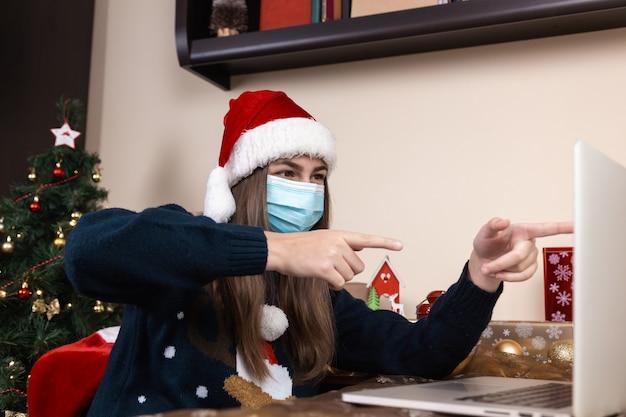 Życzenia świąteczne Online. Dziewczyna W Czapce świętego Mikołaja W Medycznej Masce Rozmawia Daje Prezent Za Pomocą Laptopa Dla Przyjaciół I Rodziców Połączeń Wideo. Pokój Jest Odświętnie Urządzony. Boże Narodzenie W Okresie Koronawirusa. Premium Zdjęcia