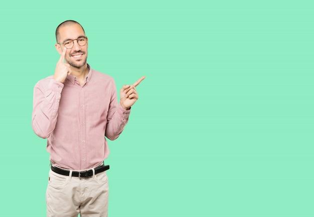 Życzliwy Młody Człowiek Robi Gestowi Ostrożność Z Ręką Wskazującą Na Jego Oko Premium Zdjęcia