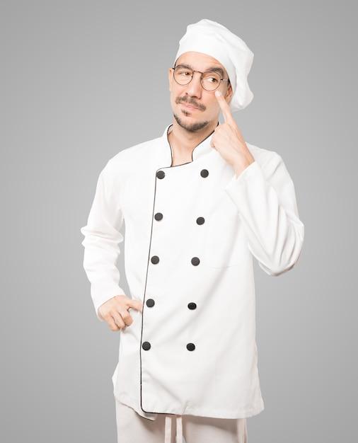 Życzliwy Młody Szef Kuchni Robi Gest Uważności Z Ręką Wskazującą Na Oko Premium Zdjęcia