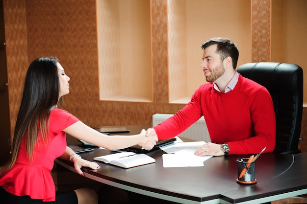 Życzliwy uśmiechnięty biznesmena i bizneswomanu handshaking Premium Zdjęcia