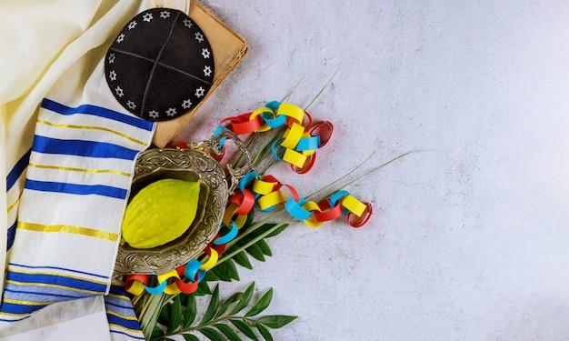 Żydowska Religijna żółta Cytron Etrogu Jest Używana Podczas święta Sukkot Jarmułki I Modlitewnika Tałejskiego Premium Zdjęcia