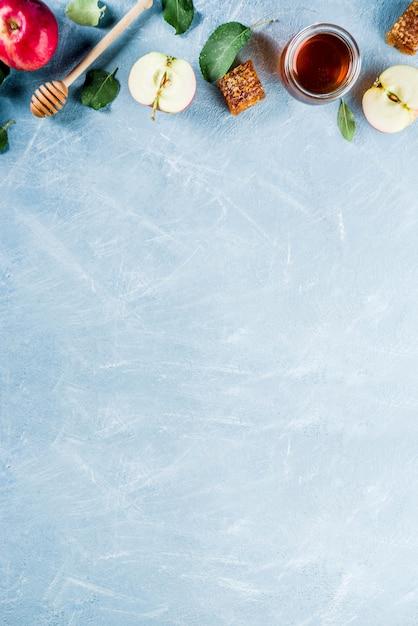 Żydowskie święto Rosz Haszana Lub Koncepcja święta Jabłka, Z Czerwonymi Jabłkami, Liśćmi Jabłka I Miodem W Słoiku, Jasnoniebieskie Tło Powyżej Premium Zdjęcia