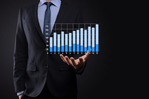 Zyskuje Biznesmen Posiadający Holograficzne Wykresy I Statystyki Giełdowe Premium Zdjęcia