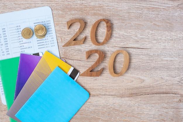 2020 feliz año nuevo con banco de libros y monedas en mesa de madera Foto Premium