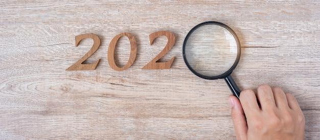 2020 feliz año nuevo con empresario sosteniendo lupa de vidrio Foto Premium