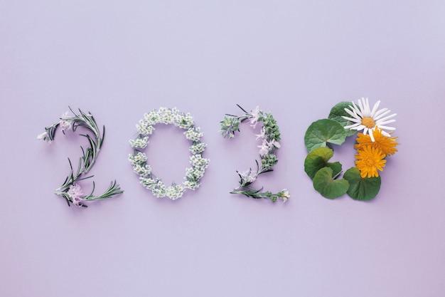 2020 hecho de hojas y flores naturales sobre fondo morado Foto Premium