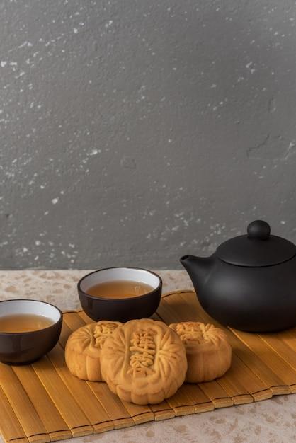 4 mini pasteles de luna de pasta de loto servidos con té chino Foto Premium