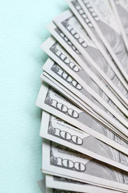 El abanico de billetes de un dólar de ee. uu. de un nuevo diseño se encuentra en un fondo azul claro Foto Premium