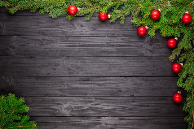 Abeto de navidad sobre fondo de madera negra Foto Premium
