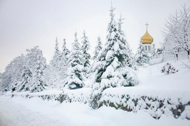 Abeto nevado helado y una iglesia con cúpula dorada en las montañas de los cárpatos, ucrania Foto Premium