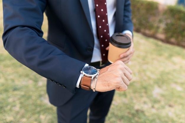 Abogado de primer plano con café mirando su reloj Foto gratis