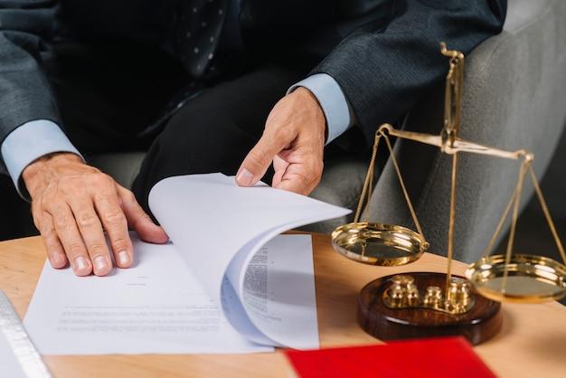 Abogado de sexo masculino que da vuelta a las páginas del documento en el escritorio con escala de justicia. Foto Premium