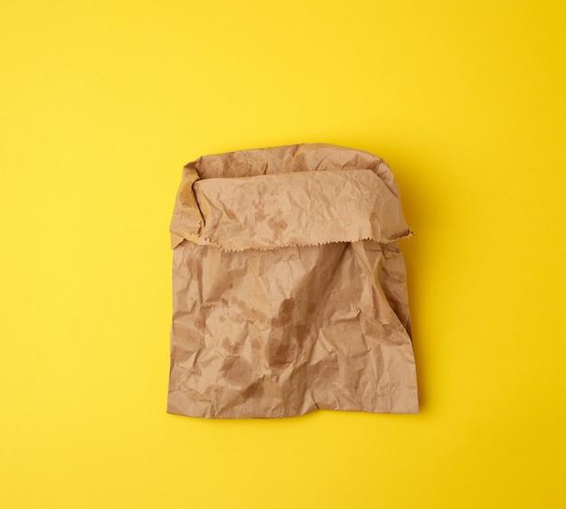 Abra la bolsa de papel marrón con manchas de grasa en amarillo Foto Premium