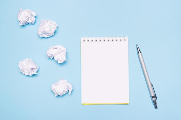 Abra el cuaderno vacío, bolígrafo y bolas de papel arrugado sobre papel azul Foto Premium