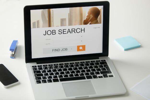Abra el portátil en el escritorio, título de búsqueda de trabajo en la pantalla Foto Gratis
