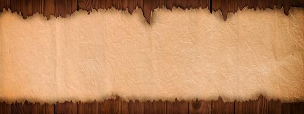 Abra la voluta antigua en una mesa de madera, fondo de papel panorámico Foto Premium