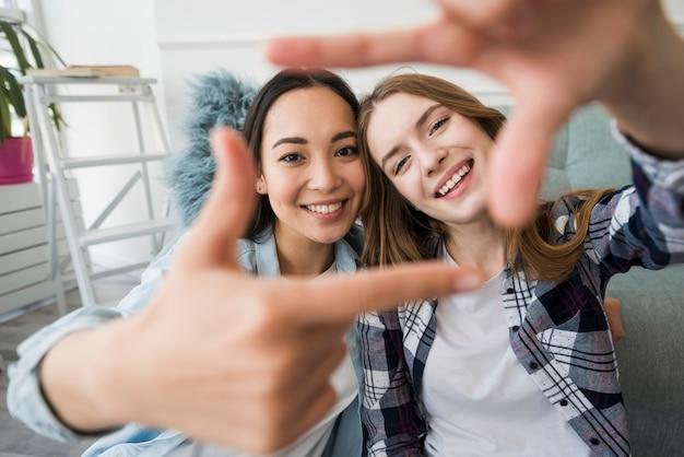 Abrazando a las chicas sonriendo y haciendo un marco de fotos con las manos como selfie Foto gratis