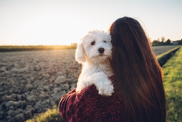 Abrazo romántico entre un perro blanco y su dueño. humanos y animales enamorados Foto Premium